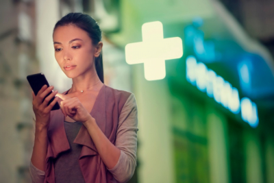 A young asian woman is locating a pharmacy store at night with her smart phone mobile device